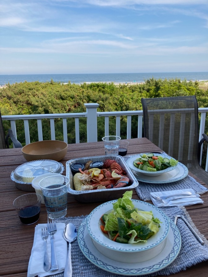 Porch table overlooking ocean, with salads and seafood platter on table.
