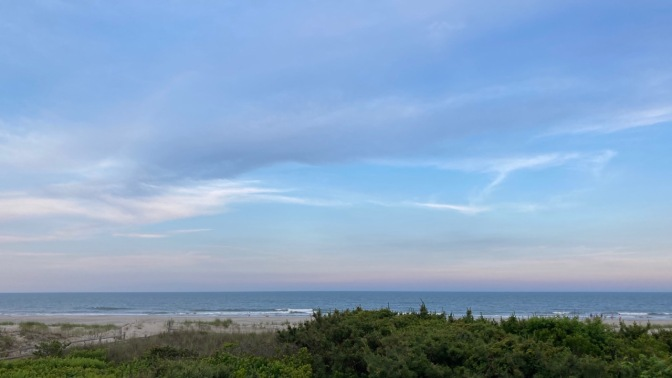 View of sky and ocean, with beach in foreground.