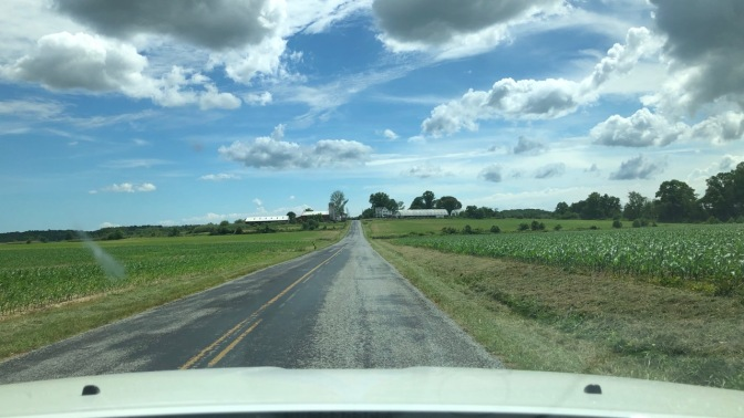 Two-lane road through farmland.