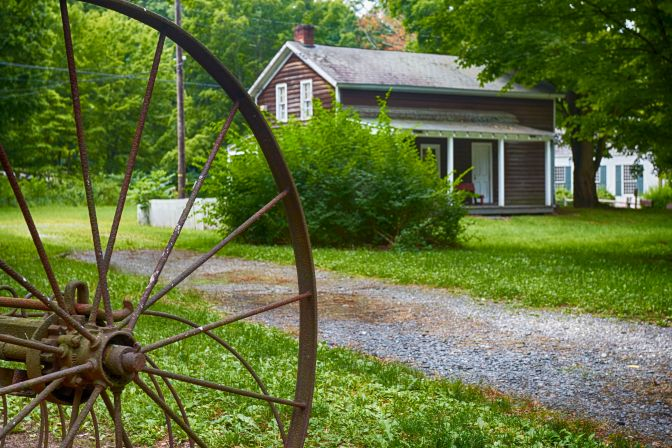 Metal wheel of harvester in foreground, with old wooden house in background.