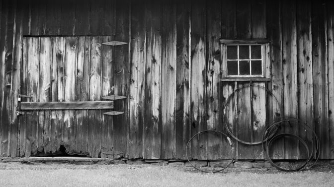 Wall of wooden house with door on left and iron wheels below window on right.
