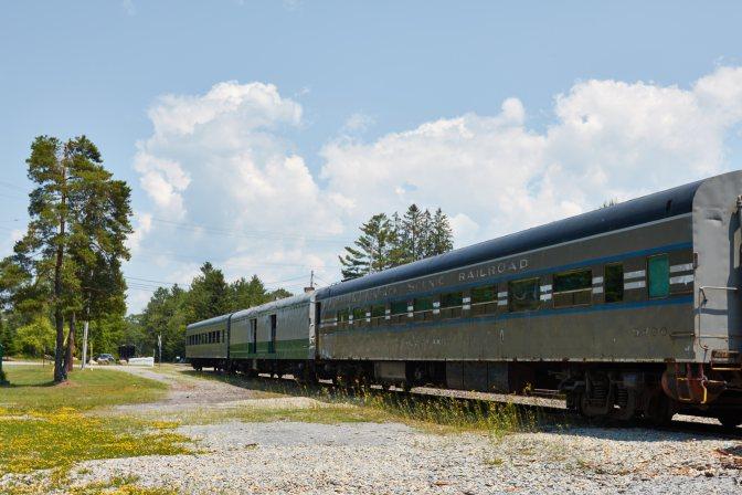Train coach cars sitting on railroad line.
