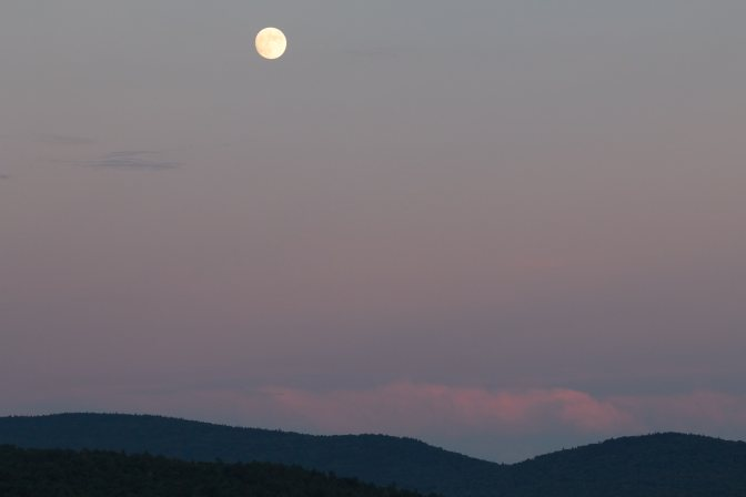 Full moon over mountains, with clouds low in the sky.