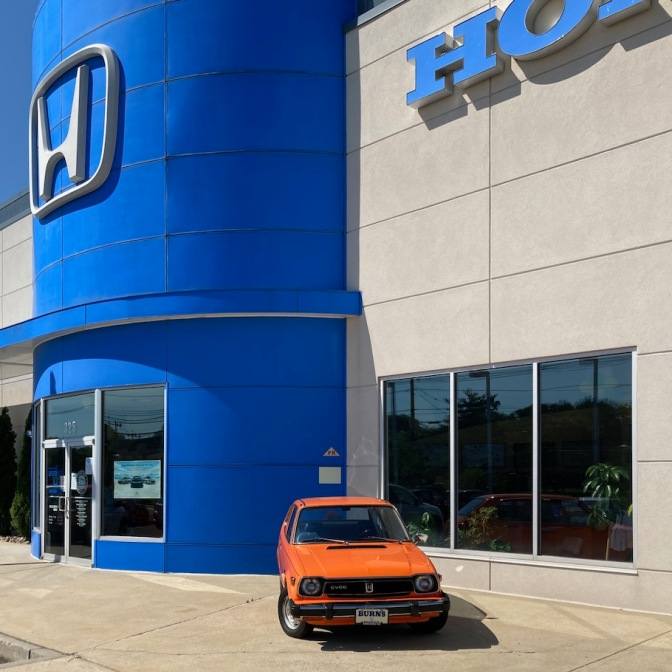 Exterior of Burns Honda, with a 1st generation orange Honda Civic parked in front of the building.