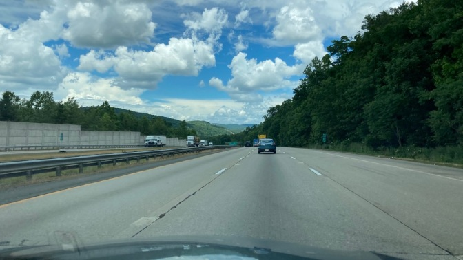 View of blue sky with clouds over NY Thruway, from behind windshield of Honda Accord.