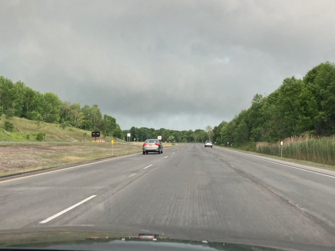 View of thunderstorms above road on New York Thruway.