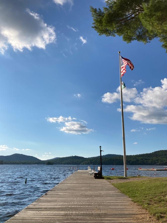 US flag atop flagpole beside dock along Fourth Lake.