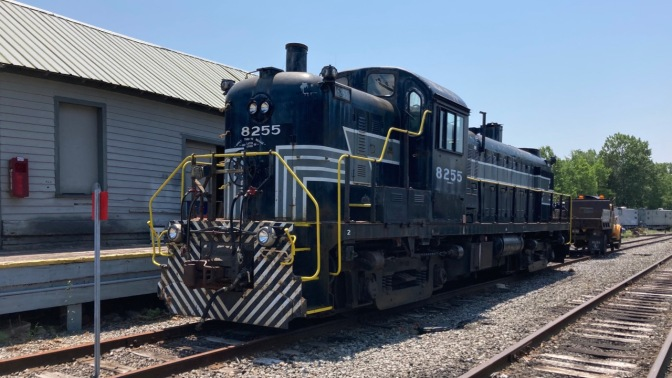 Black railroad engine alongside maintenance depot.