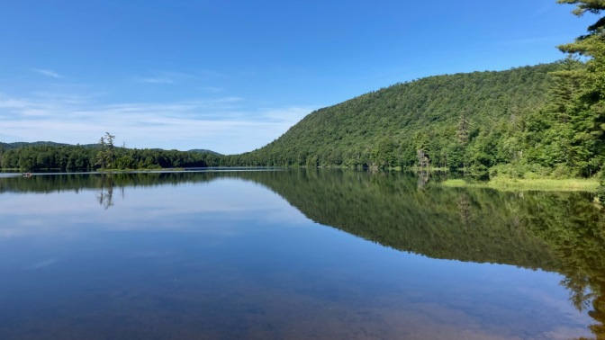 View of Moss Lake, with a reflection of the mountain and shoreline in the lake.