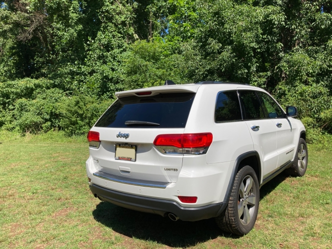 White Jeep Grand Cherokee parked on a grassy field.
