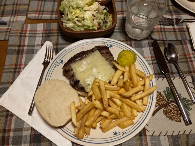 Cheeseburger and french fries on plate, with a salad in a bowl next to the plate.