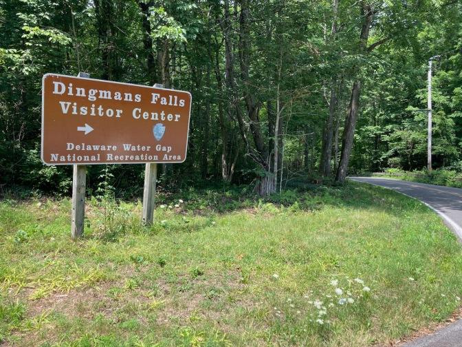 Sign for Dingmans Falls Visitor Center beside road.
