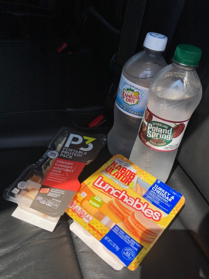 Photo of two bottles of water, a pack of Lunchables, and a snack pack on car seat.