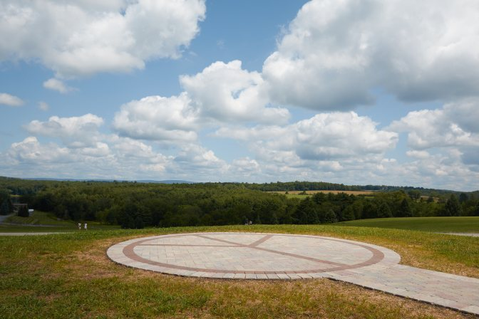 Large stone peace circle in field.