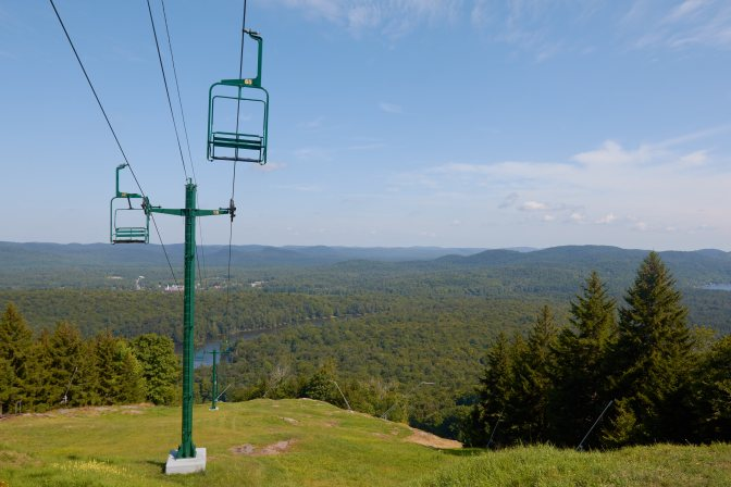 View of chair lift on mountain, with mountains and forests in distance.