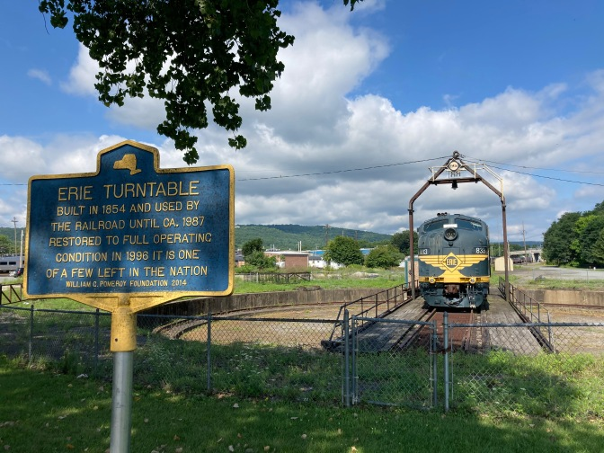 Train in background, with blue sign on pole that reads ERIE TURNTABLE BUILT IN 1854 AND USED BY THE RAILROAD UNTIL CA. 1987 RESTORED TO FULL OPERATING CONDITION IN 1996 IT IS ONE OF A FEW LEFT IN THE NATION