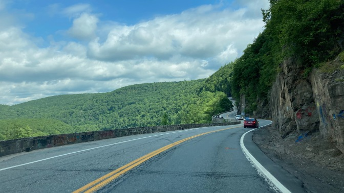 View of Route 97 through mountains, with cliffs on right side of road.