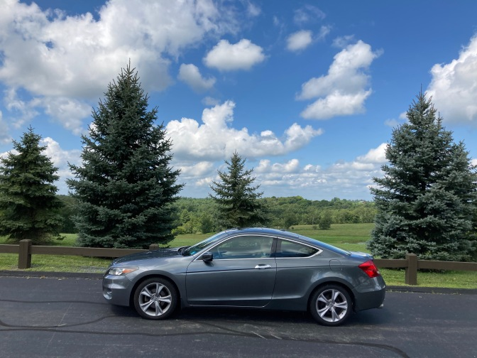 2012 Honda Accord coupe, parked in front of tree-lined hills.