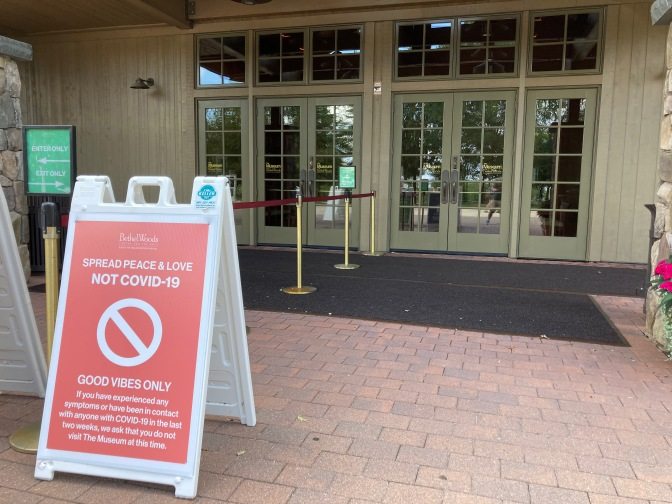 Sign outside of entrance doors to Bethel Woods Center, that says SPREAD PEACE & LOVE NOT COVID-19.
