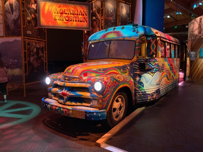 Bus painted in hippie colors with words and murals on it.
