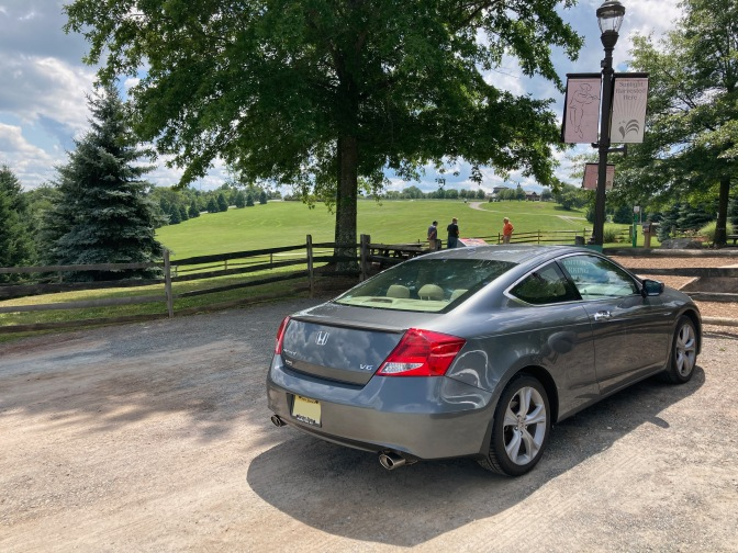 2012 Honda Accord parked in gravel lot, with field in the background.