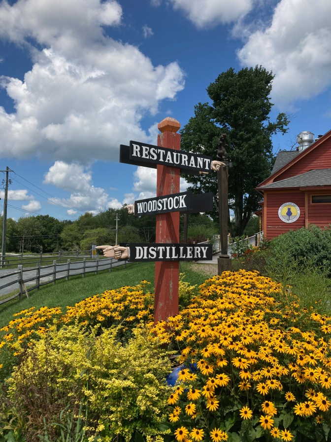 Three-way sign indicating Restaurant, Woodstock, and Distillery.