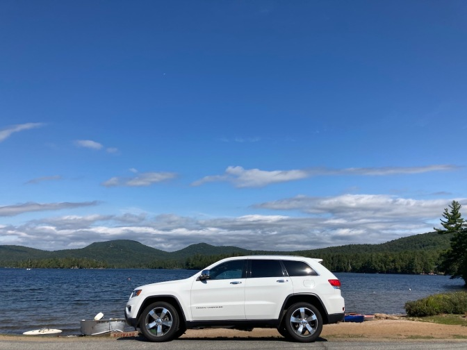 White Jeep Grand Cherokee parked in front of Blue Mountain Lake.
