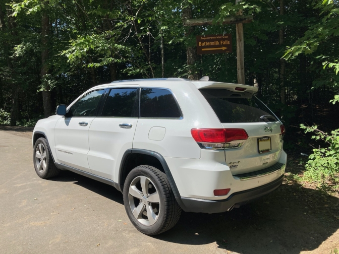 White Jeep Grand Cherokee in front of sign that says BUTTERMILK FALLS