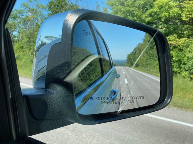 Car rearview mirror, with mountains in distance of mirror.