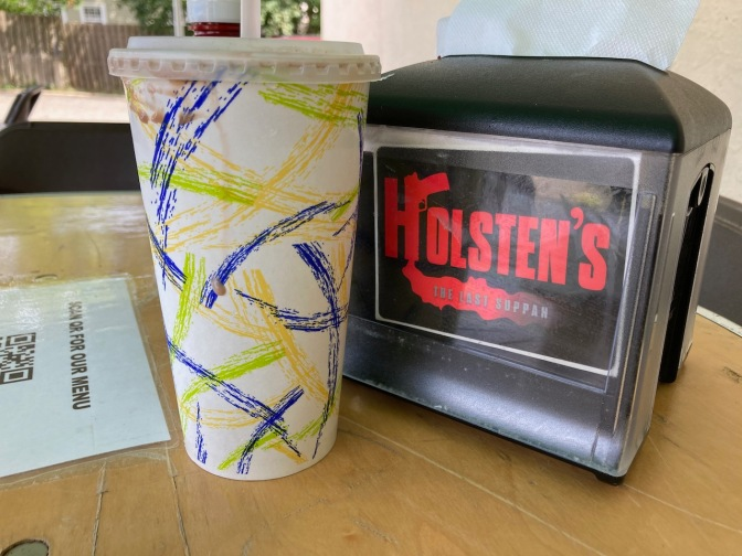 Paper cup beside napkin holder that says HOLSTEN'S THE LAST SUPPAH.