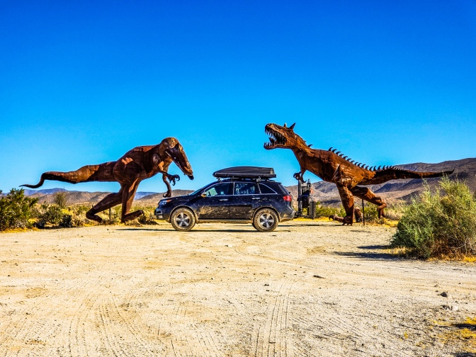 Acura MDX in front of two dinosaur sculptures.
