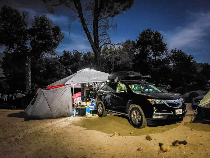 Black Acura MDX parked in front of camping tent.