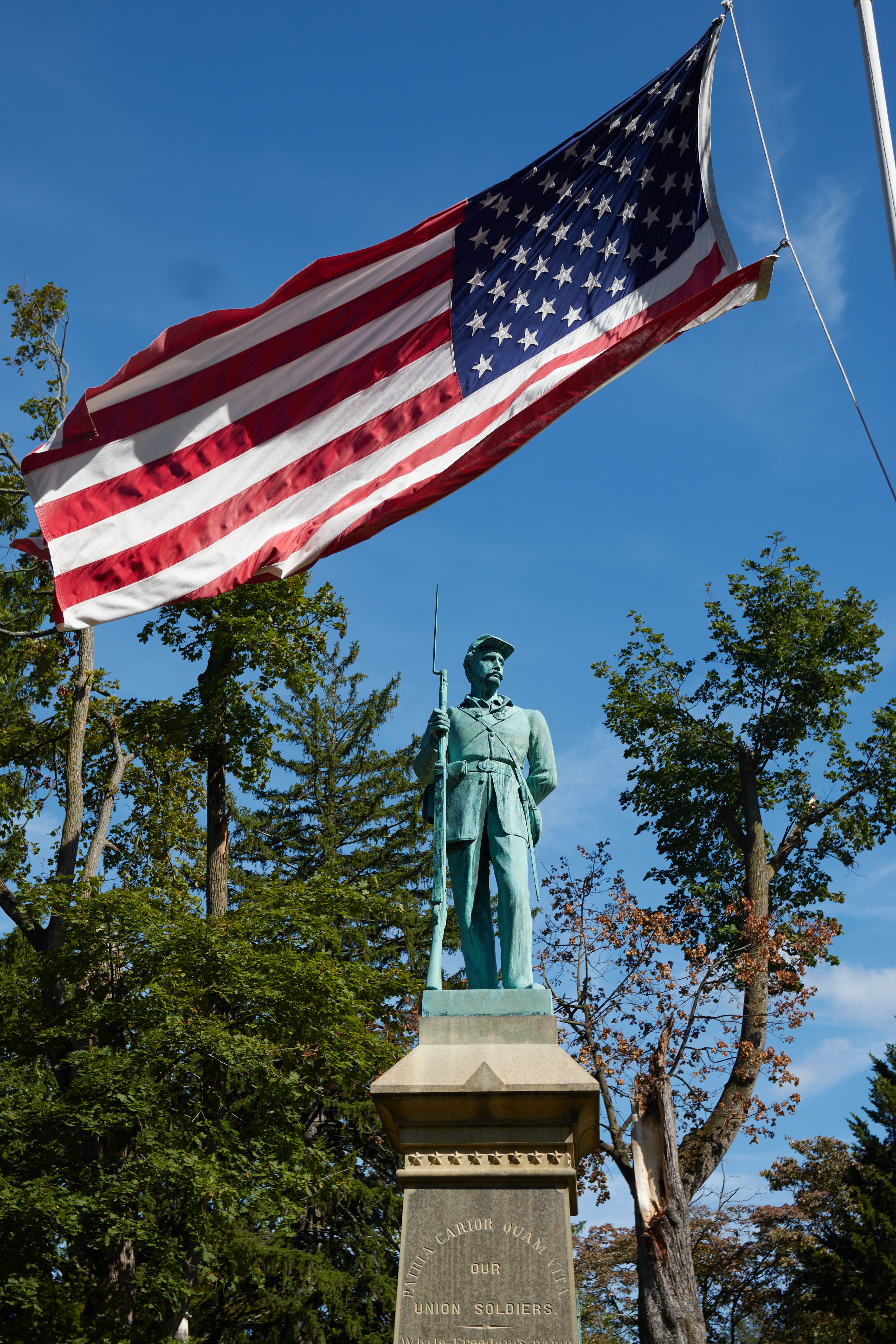 Civil war Monument, with American flag flying above sculpture of soldier.