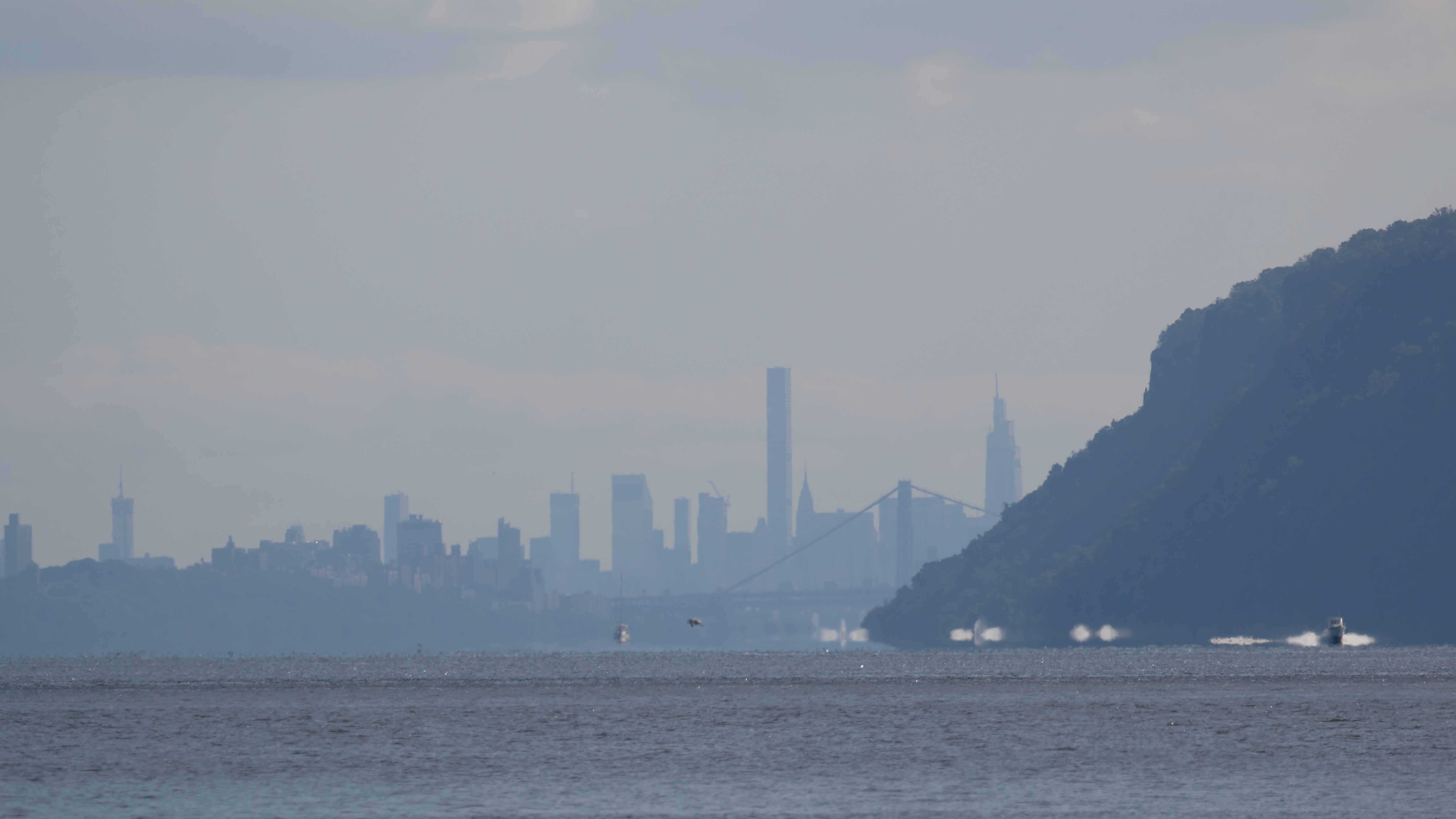 View of bluffs along Hudson River, with Manhattan skyline in background.