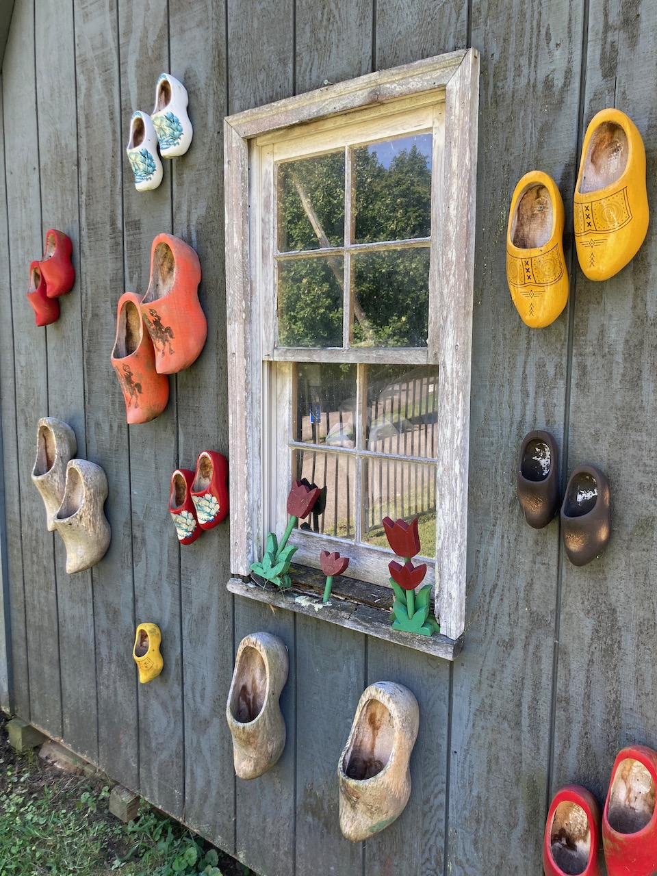 Clogs nailed to side of shed in cemetery.