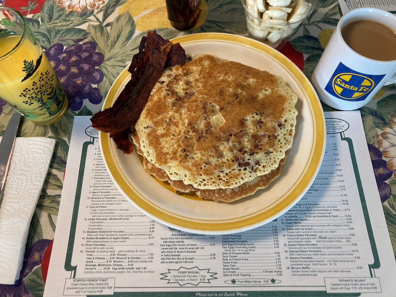 Plate with pancakes and bacon, glass of orange juice, and mug of coffee.