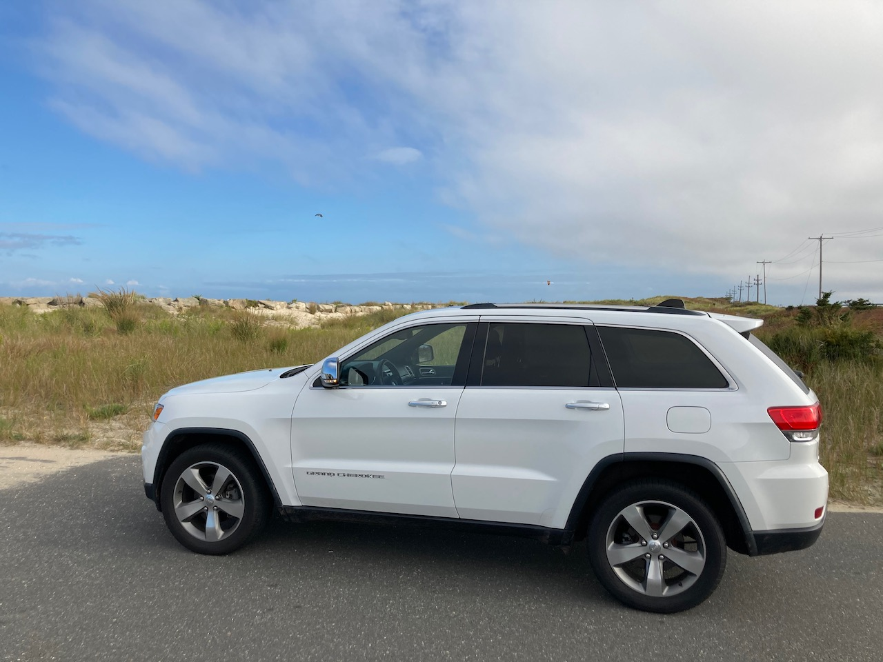 2014 Jeep Grand Cherokee parked by dunes.