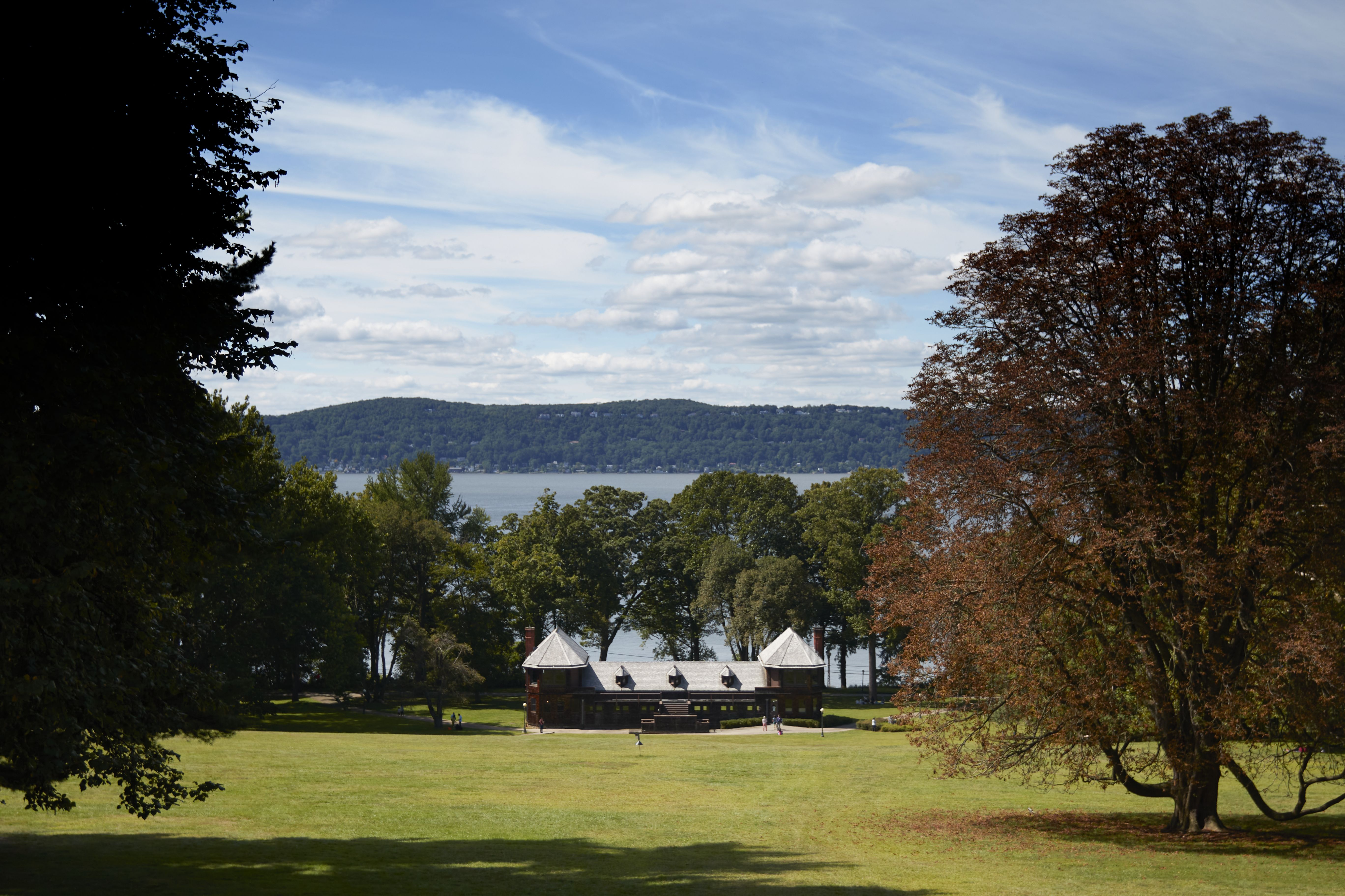 View of bowling alley down sloping grass hill, with Hudson River in background.