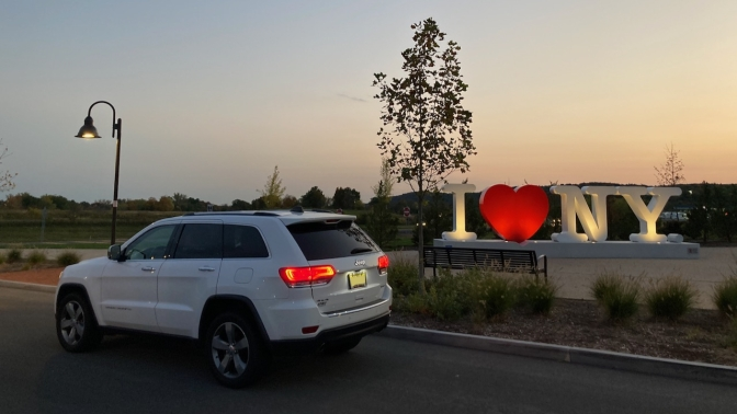 2014 white Jeep Grand Cherokee parked in front of I LOVE NEW YORK sign.
