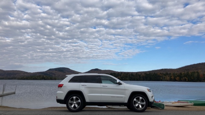 2014 Jeep Grand Cherokee parked in front of Blue Mountain Lake.