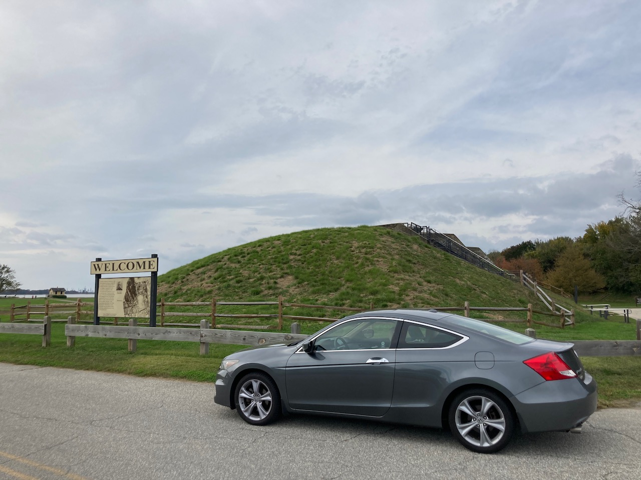 2012 Honda Accord parked in front of an earthenwork fort, with WELCOME sign in background.