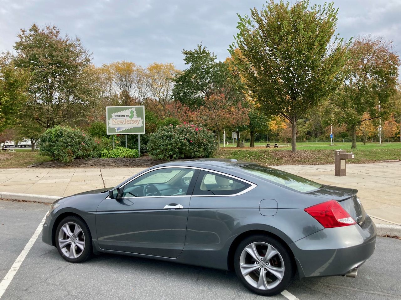 2012 Honda Accord parked beside WELCOME TO NEW JERSEY sign.