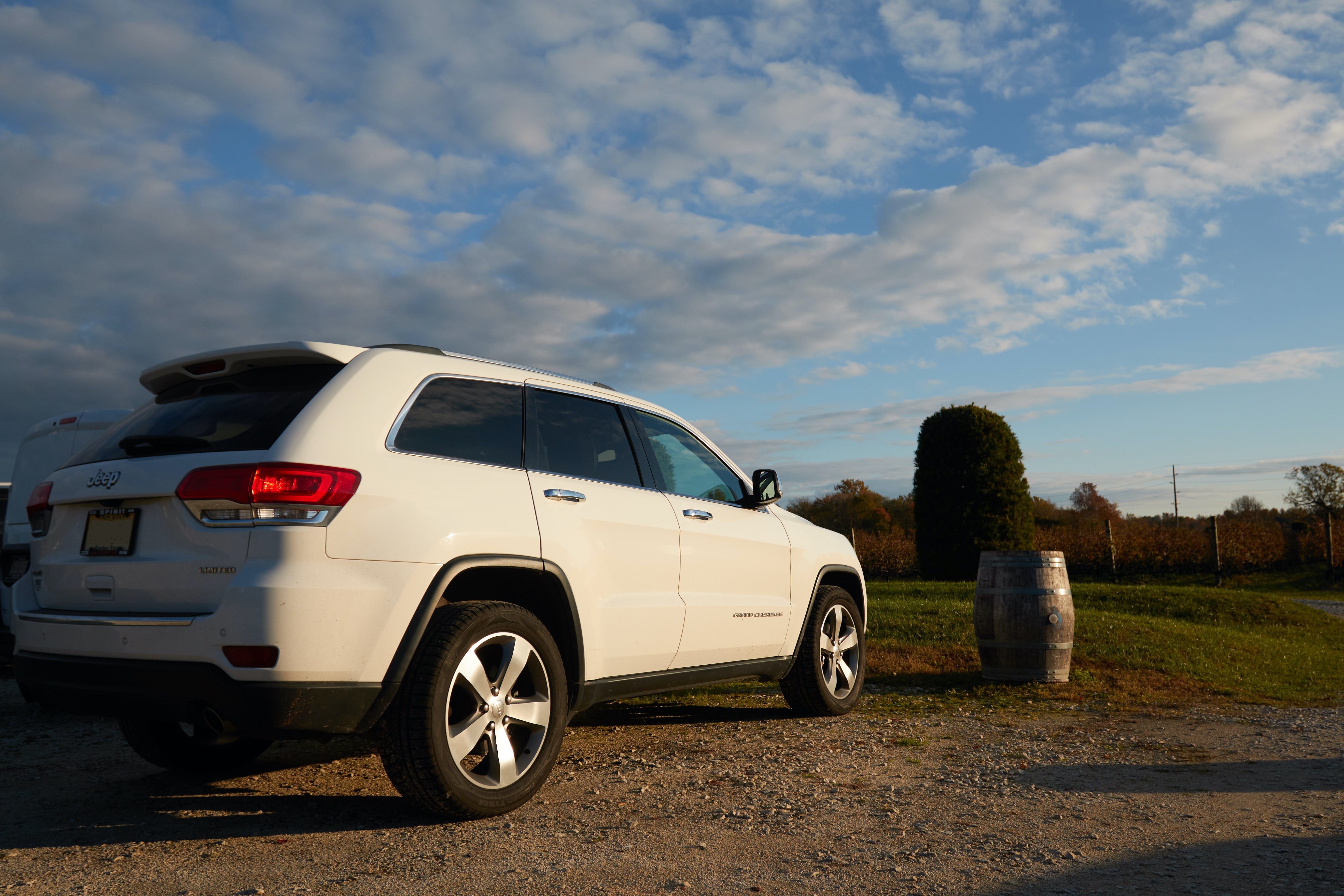 2014 White Jeep Grand Cherokee parked in vineyard.