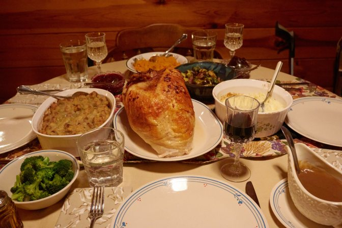 Table with turkey, stuffing, gravy, broccoli, brussel sprouts, sweet potatoes, and coleslaw.