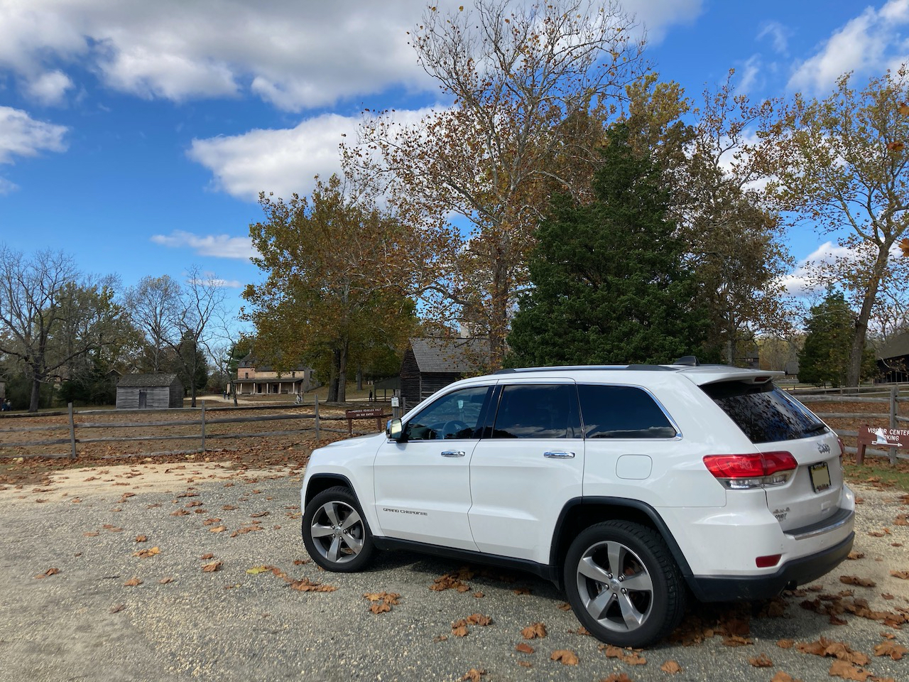 White 2014 Jeep Grand Cherokee parked in front of historic village.