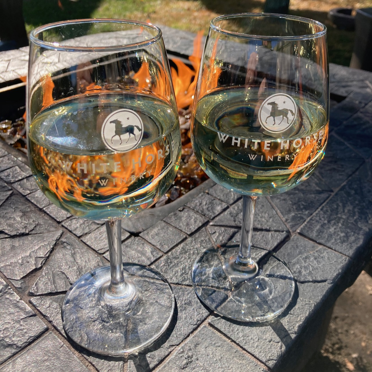 Two glasses of wine in front of fire pit.