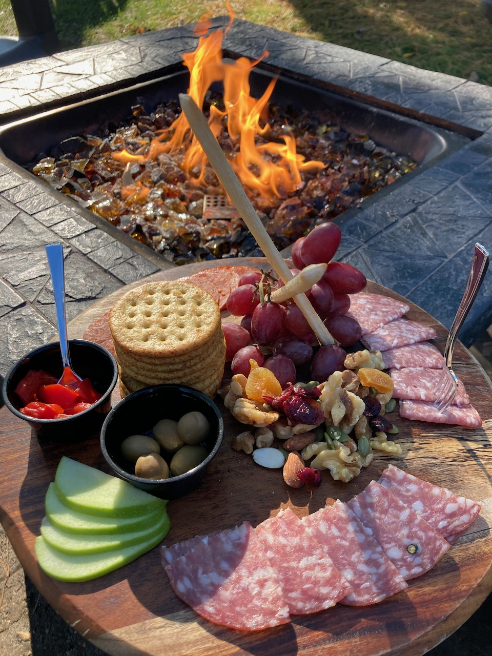 Cheese and fruit spread on wooden platter beside fire pit.