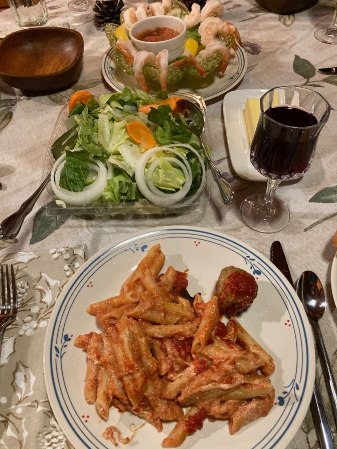 Pasta and meatballs on plate, with glass of wine, tossed salad, and shrimp cocktail on table.