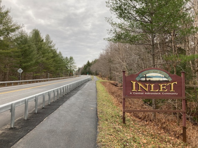 TOBIE trail beside Route 28 in Inlet. A sign by side of road says INLET A CENTRAL ADIRONDACK COMMUNITY.