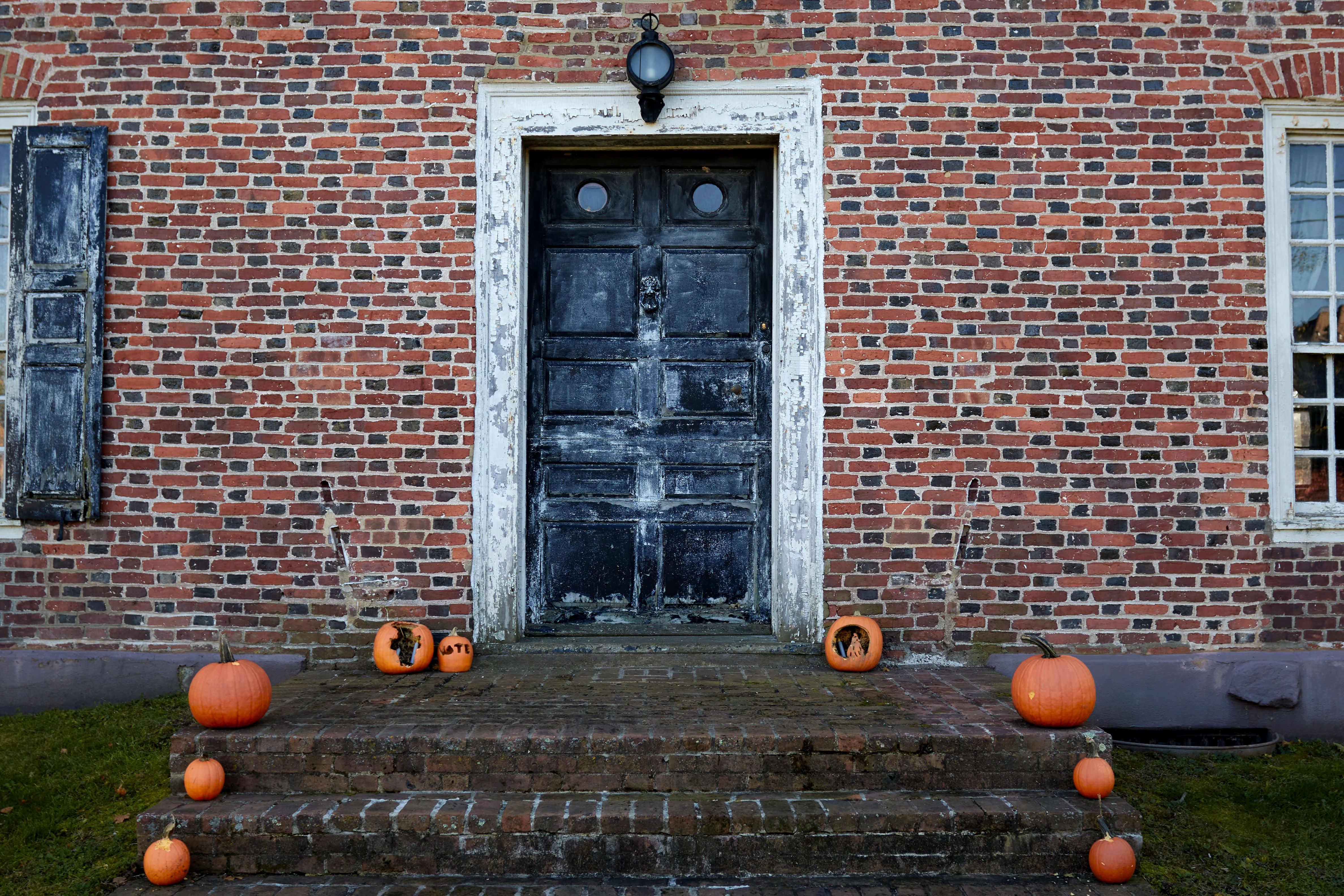 Entrance to Old Dutch Parsonage, with jack o'lanterns along sides of front steps.